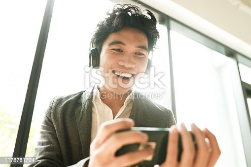 Asian young man is surprising new function on his phone mobile app.
