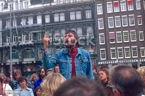 Rotterdam, Netherlands, 1978. Young man holds a speech to passers-by on a public square in Rotterdam. Furthermore: buildings.