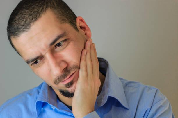 young man is having toothache. - mandibula fotografías e imágenes de stock