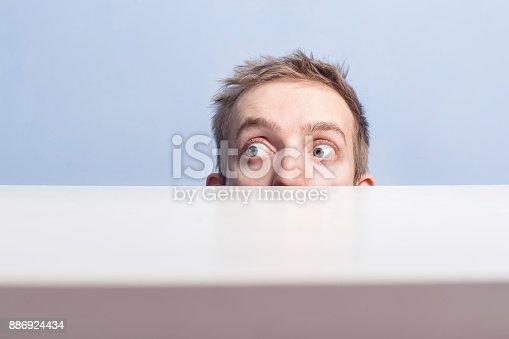 istock Young man is hidinge. Spying. 886924434