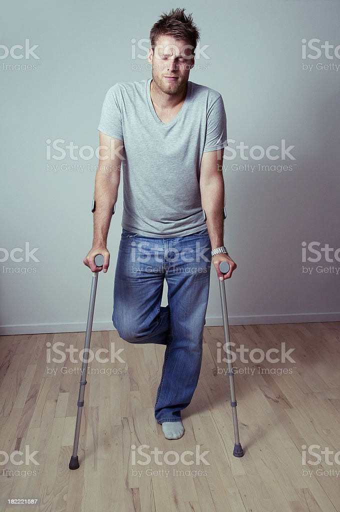 Young man is in pain and is supported by crutches royalty-free stock photo