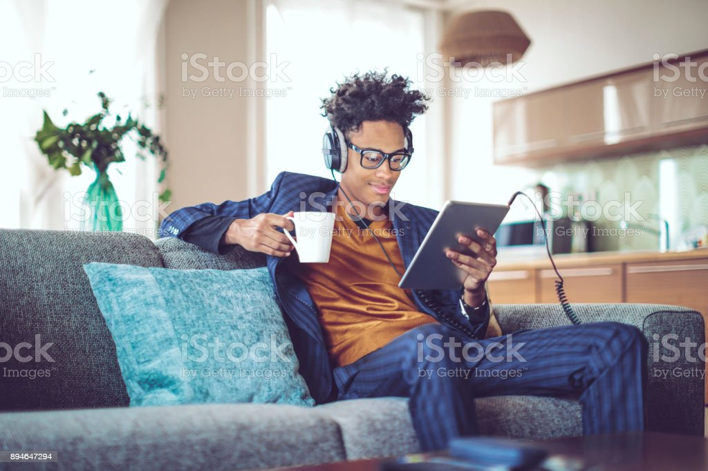 Young man is listening music at home stock photo