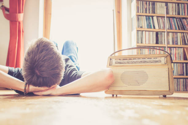 young man is listening to a vintage radio - radio foto e immagini stock