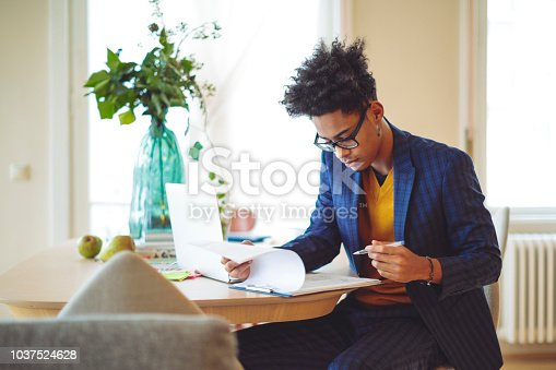 Young man is making a budget at home