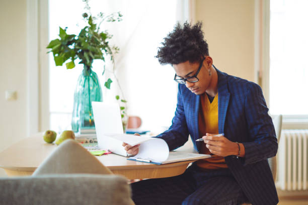 young man is making a budget at home - checklist stock photos and pictures