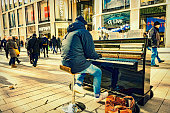 A young man is playing a transportable piano in the shopping arcade in the City of Hamburg