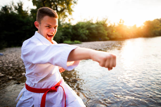 Young man  is practicing karate in nature