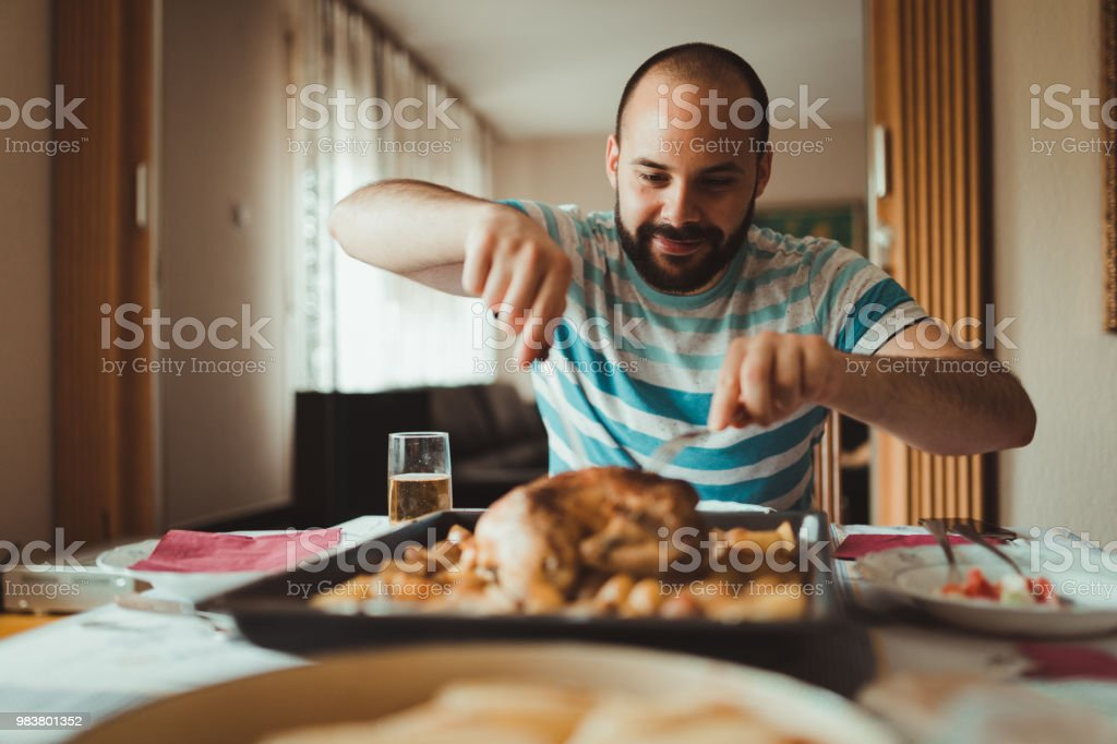 Young man is preparing to eat roast chicken at home stock photo