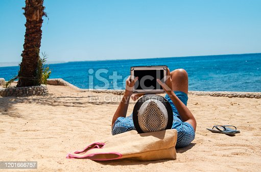 Young Man is reading on the beach with e-reader or surfing the net online with wifi connection.Relaxing with portable device.Copy space