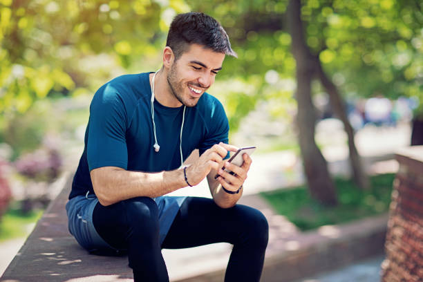 Young man is resting and texting in the park after run stock photo