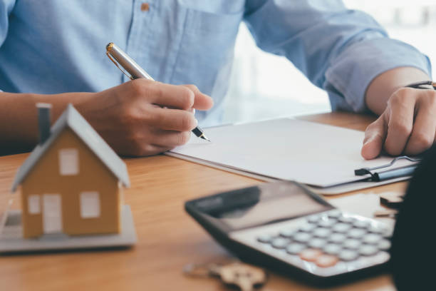 Young man is signing financial contract with real estate agent at selling office. stock photo