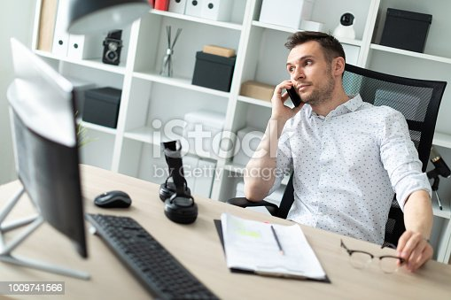 istock A young man is sitting at a table, talking on the phone and holding glasses in his hand. 1009741566