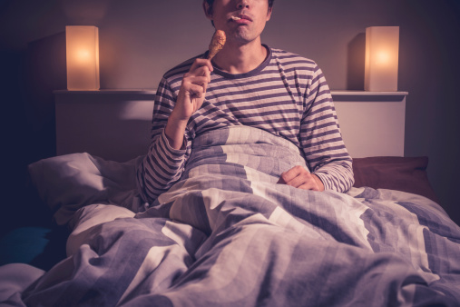 Young Man Is Sitting In Bed And Eating Chicken Stock Photo - Download Image Now