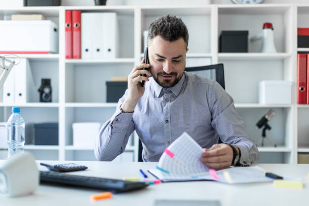 A young man is sitting in the office, talking on the phone and working with documents. stock photo