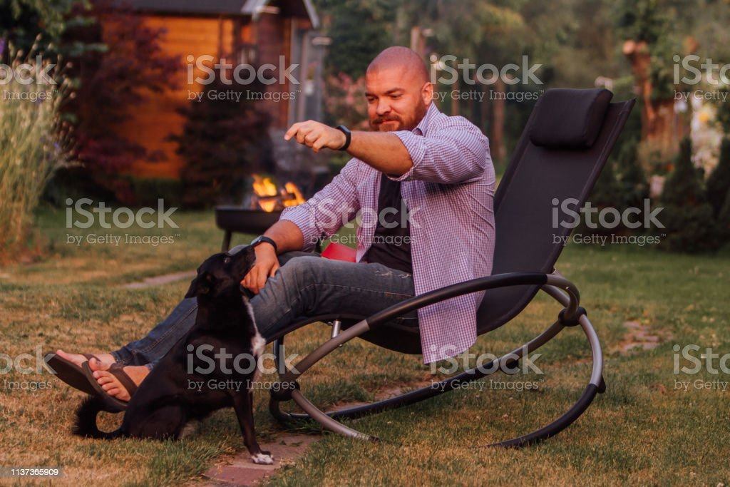 Picture of: Young Man Is Sitting On The Rocking Chair And Playing With Little Black Dog In The Garden Stock Photo Download Image Now Istock