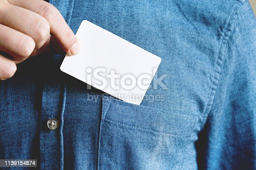 Young man is taking a blank card in the pocket of his shirt. Close up.