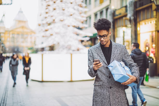 young man is texting and holding a christmas present - online shopping imagens e fotografias de stock