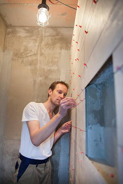 junger mann tiling. tiler bei der arbeit - keramik fliesen handwerk stock-fotos und bilder