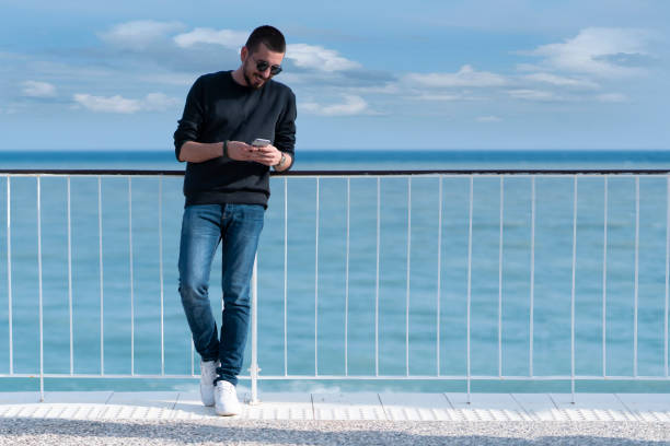 Junger Mann benutzt sein Telefon am Strand – Foto
