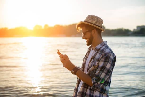 Young man is using his phone on  beach stock photo
