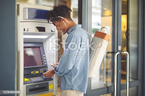 Young man is withdrawing money from an ATM
