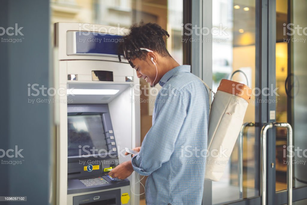Young man is withdrawing money from an ATM stock photo