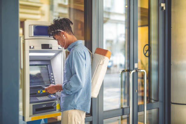 Young man is withdrawing money from an ATM Young man is withdrawing money from an ATM banks and atms stock pictures, royalty-free photos & images