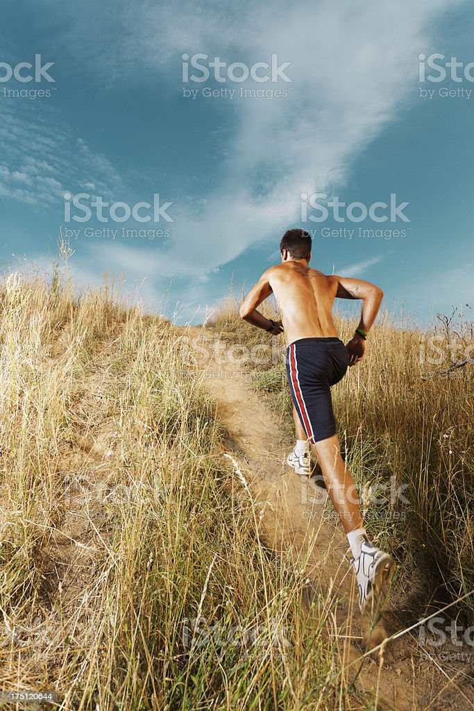 A young man jogging in an open field royalty-free stock photo