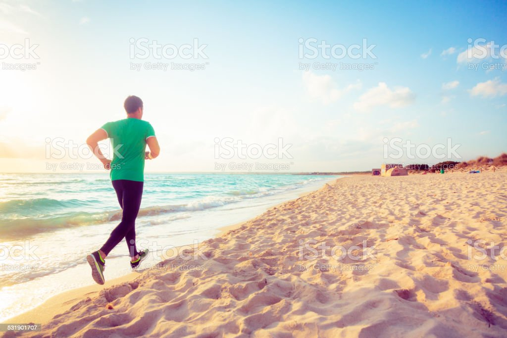 young man jogging on the beach stock photo