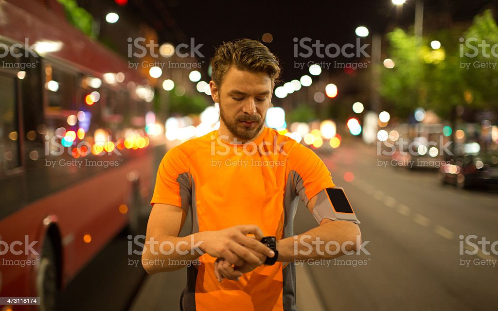 Young man jogging through the city at night. stock photo