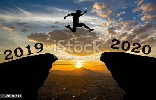 A young man jump between 2019 and 2020 years over the sun and through on the gap of hill  silhouette evening colorful sky. happy new year 2020.