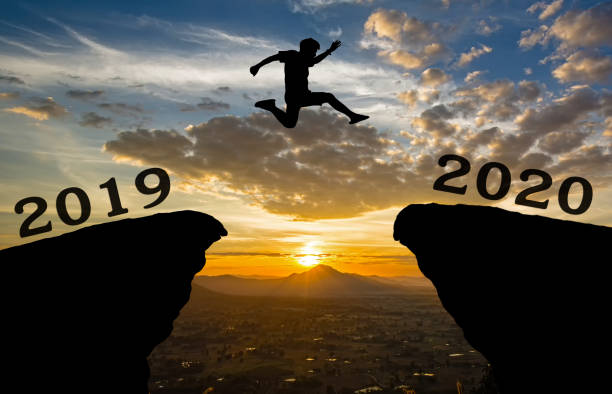A young man jump between 2019 and 2020 years over the sun and through on the gap of hill  silhouette evening colorful sky. happy new year 2020. A young man jump between 2019 and 2020 years over the sun and through on the gap of hill  silhouette evening colorful sky. happy new year 2020. between stock pictures, royalty-free photos & images
