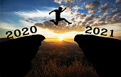 istock A young man jump between 2020 and 2021 years over the sun and through on the gap of hill  silhouette evening colorful sky. 1189545749