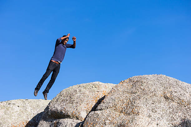 young man jumping across boulders - carolinemaryan stock pictures, royalty-free photos & images