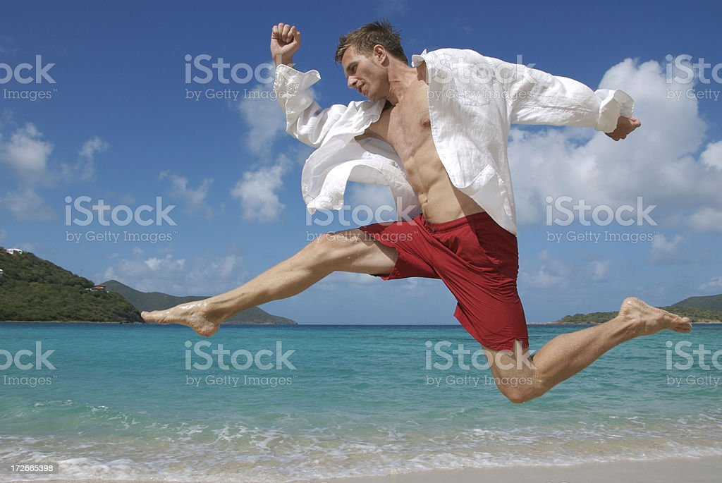Young Man Jumping Across Tropical Beach royalty-free stock photo