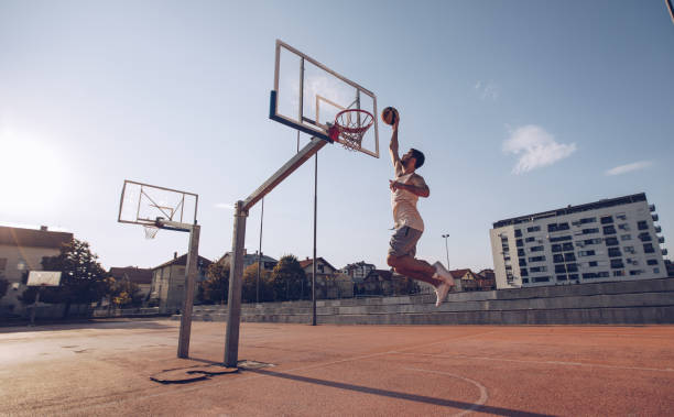 Young man jumping and making a fantastic slam dunk Young man jumping and making a fantastic slam dunk playing street ball, basketball. Urban authentic. slam dunk stock pictures, royalty-free photos & images