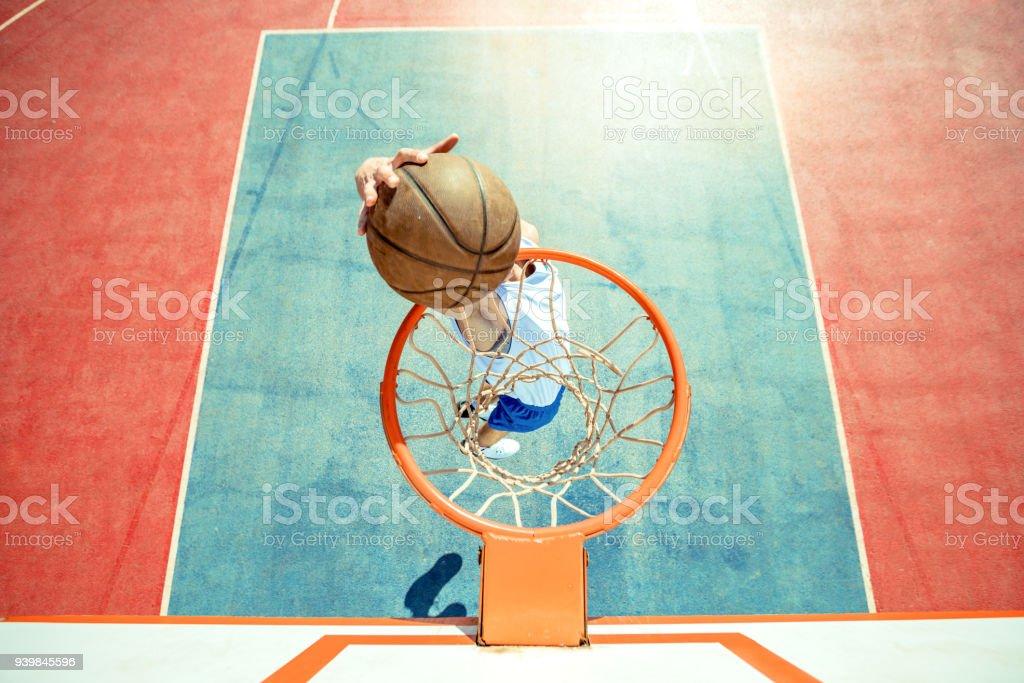 Young man jumping and making a fantastic slam dunk playing street ball, basketball. Urban authentic. stock photo