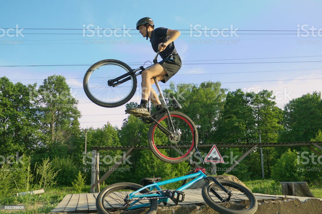 Young man jumping and riding on a BMX bicycle downhill stock photo