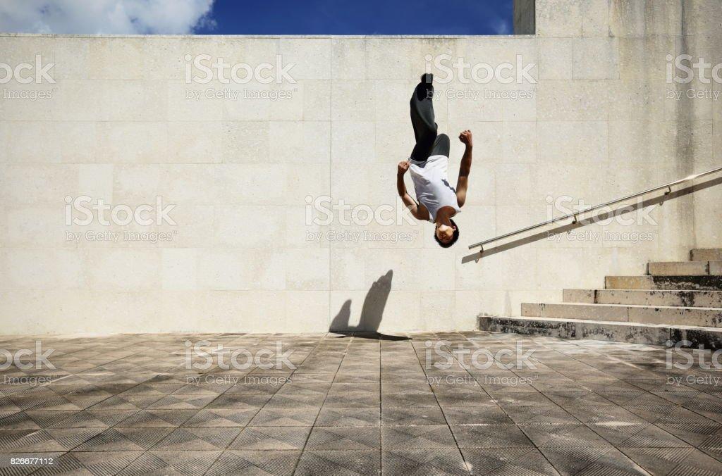 Young man jumping at back flip stock photo
