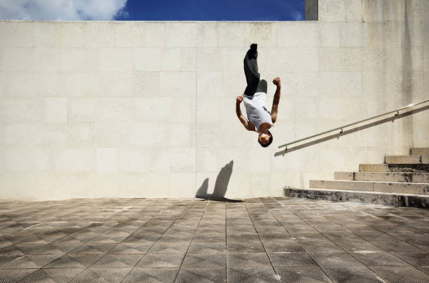 Young man jumping at back flip stock photo