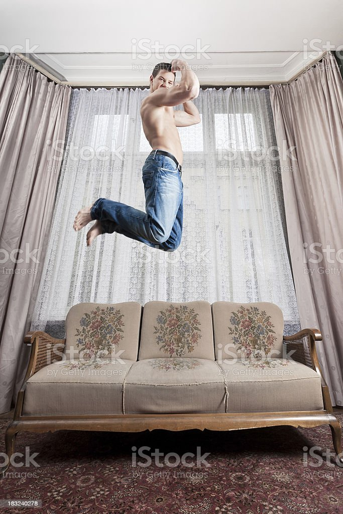 Young man jumping, celebrating in hotel room stock photo