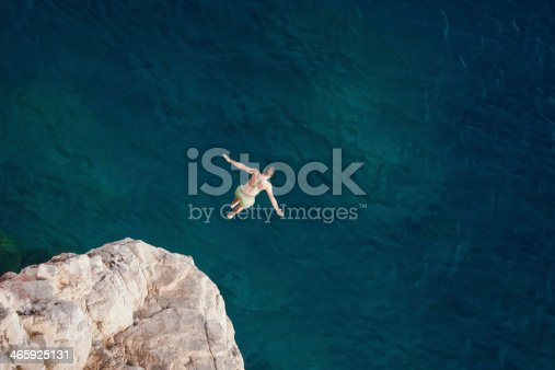 istock Young man jumping from cliff into sea. 465925131