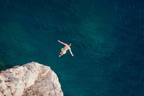 młody człowiek skoki z klifu do morza. - klif zdjęcia i obrazy z banku zdjęć