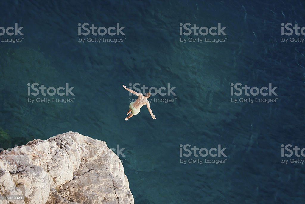 Young man jumping from cliff into sea. stock photo