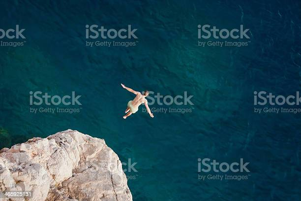 Photo of Young man jumping from cliff into sea.