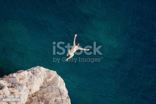 istock Young man jumping from cliff into sea. 465929855