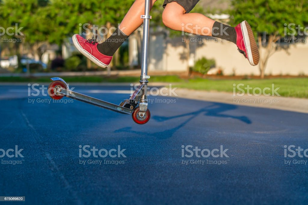 Young Man Jumping High on Scooter stock photo