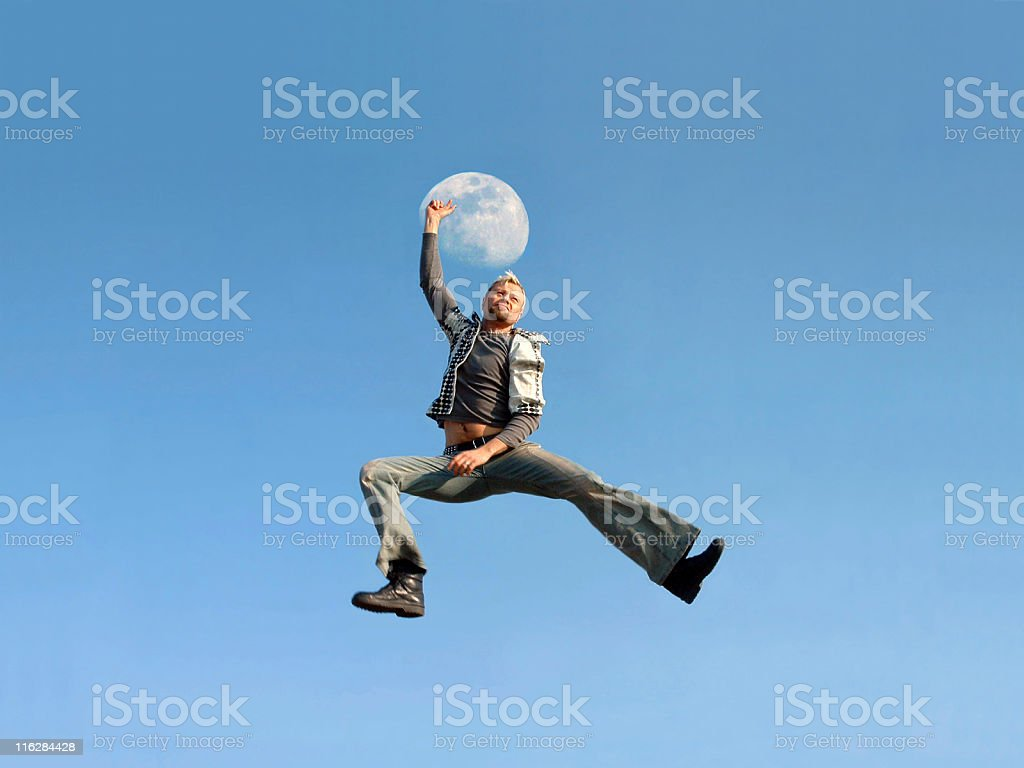 Young man jumping in front of the moon royalty-free stock photo