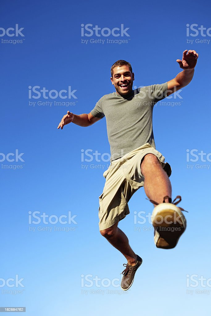 Young man jumping in mid air against the blue sky royalty-free stock photo