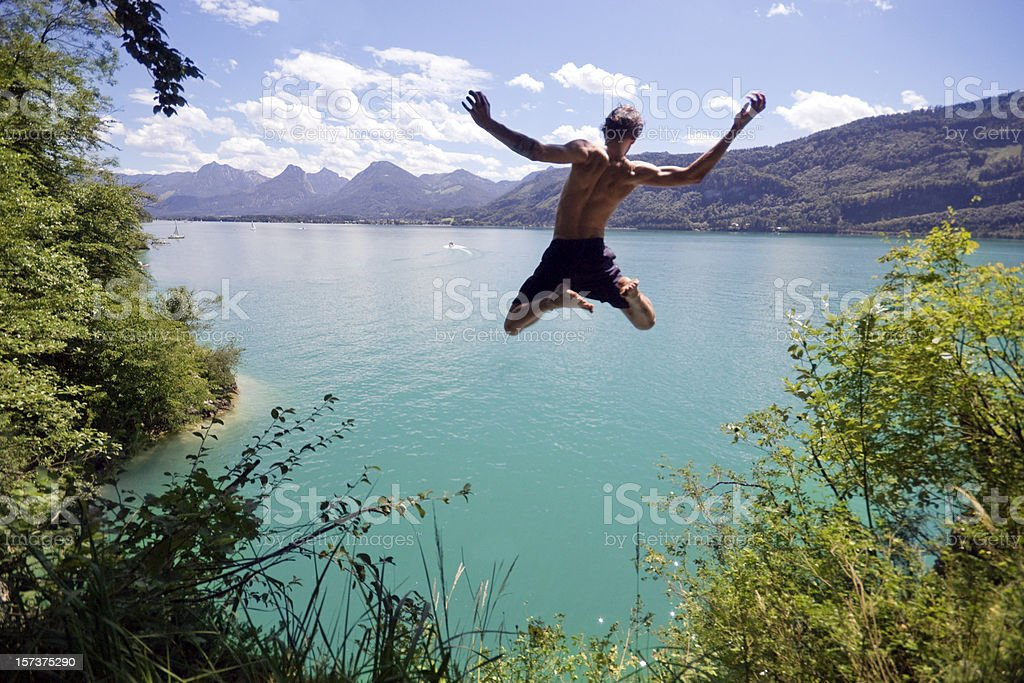 Young man jumping into blue water on a sunny day stock photo